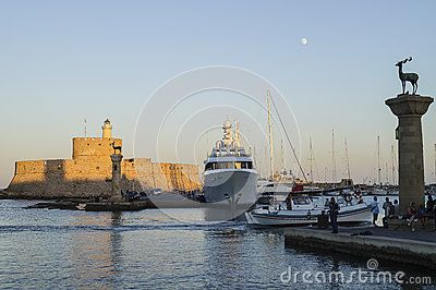 Ships and boats in port in Rodhes town , Rodhes Island , Greece. View on the old lighthouse and castle. Evening time.