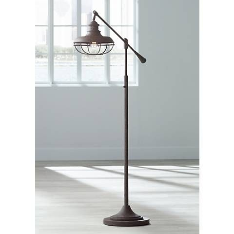 Finished in earthy rust this metal boom floor lamp features an industrial inspired cage