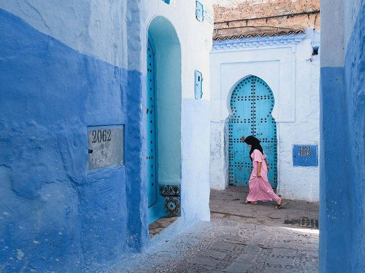 A girl in a pink dress stands out against the bright blue of a doorway in Chefchaouen, Morocco, in this National Geographic Photo of the Day.