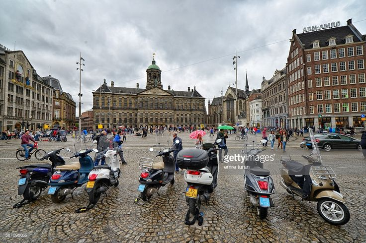 dam square and royal palace with parked bikes in the foreground on a rainy Autumn afternoon in Aamsterdam.