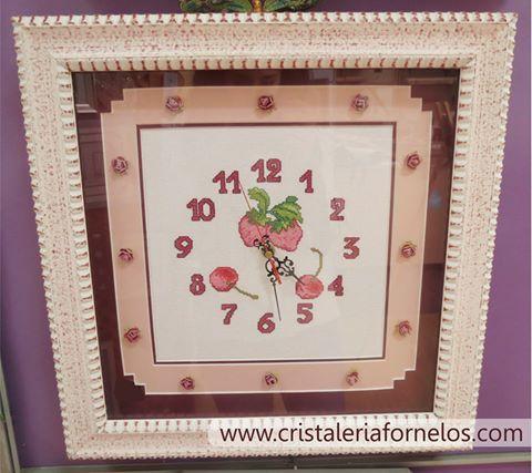 Reloj enmarcado con un cuadro en tonos beige con reflejos en color guinda , con dos passpertú, uno de ellos con formas y flor seca