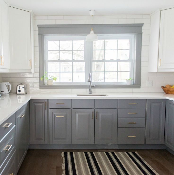 A gray and white IKEA kitchen renovation. Check out this two-toned kitchen design with marble quartz countertops, subway tile backsplash and gold hardware.