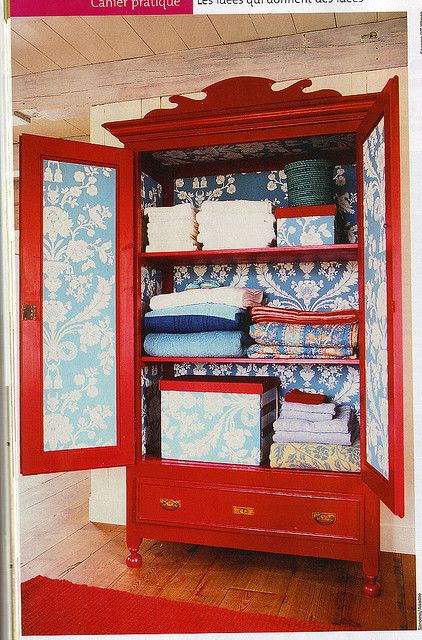 Red armoire with wallpaper inside.