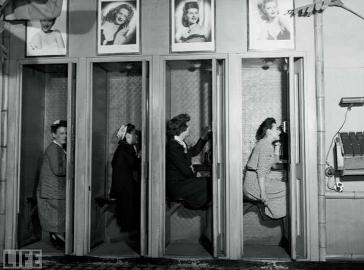 THE VANISHING OLD-SCHOOL TELEPHONE BOOTHS OF NYC. I'm not talking about any old pay phones, I'm talking about the actual phone booths. Like the ones in the bank of vintage phone booths in the photo. Gordon Parks 1943 image of four women inside the Hurricane Ballroom in NYC. Rack of phone books off to the right. You would step in, close the squeaky door, the light would come on, and so would the fan. Somehow there was an intimacy, and feeling of privacy about these tiny spaces. When that door…