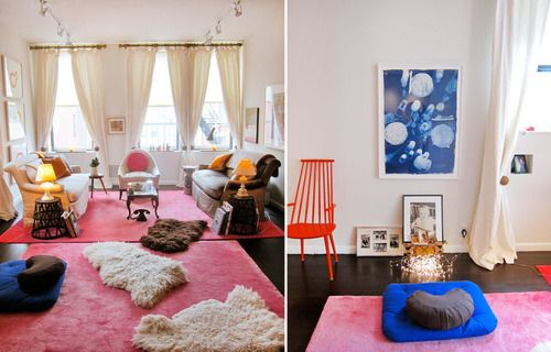 This quirky New York City home has dark flooring, hot pink area rugs, floor-to-ceiling curtains, track lighting, sheep skin throws and eclectic furniture.