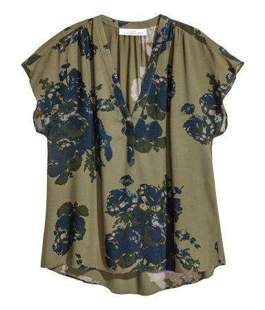 Kakigrøn/Blomstret. Bluse med V-udskæring i blød, vævet viskose med trykt mønster. Blusen har rynkning på skuldrene og korte ærmer. Lige model med lidt