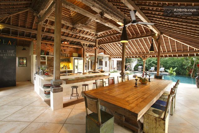 A large outdoor kitchen furnished with unique Indonesian pieces in a teak guesthouse in Bali.