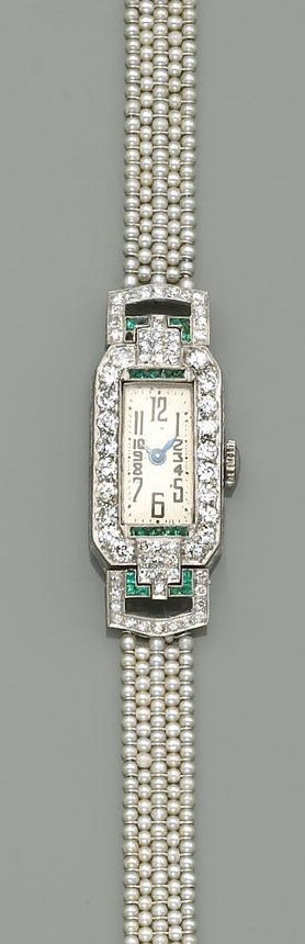 An art deco lady's, Swiss diamond, emerald and seed pearl wristwatch  the rectangular-shaped dial framed by round brilliant-cut diamonds to single-cut diamond set shoulders, accented by French-cut emeralds, on a seed pearl strap, and completed by an old European and round brilliant-cut diamond clasp; estimated total diamond weight: 1.45 carats; overall length: 7 in.