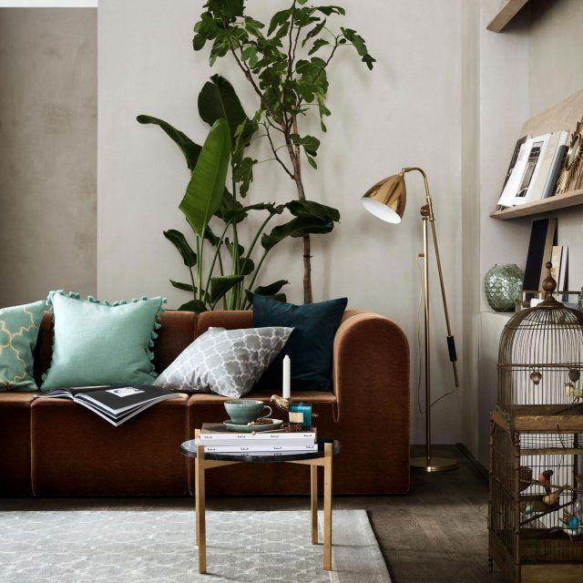 Un salon qui allie style vintage avec la cage à oiseaux et la lampe et green power avec les plantes et les coussins colorés, à merveille.