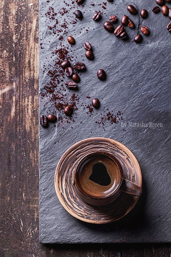 For Coffee Lovers - Brown ceramic cup of coffee and coffee beans over black slate as background. With copy space at right. Top view.