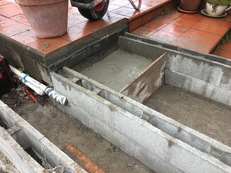 I drilled holes and inserted 3 deformed reinforcing bars then poured a concrete block to support the pool deck as the blocks here were just sitting on dirt
