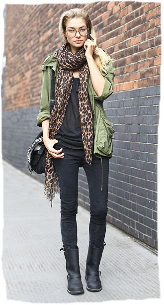 """Feelin' feisty today? Here's a mild rock version to try. I like how the baggy shirt, and green army """"inspired"""" coat keeps the style current and somewhat soft, while the black skinny jeans, biker boots and bag give it a hard edge. Also love how the leopard print scarf works to breaks up the solids with matching brown glasses."""