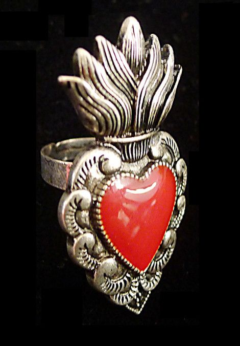 Based on the Mexican tin heart wall decorations, this solid metal cast ring has a vintage silver finish with red resin heart filling. Comes with reinforced, adjustable band, so it fits most finger siz