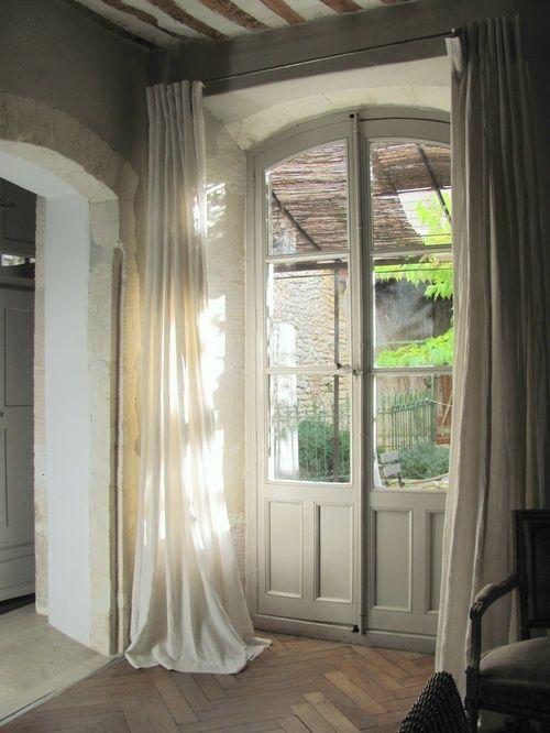 Uma construção antiga, com portas francesas também antigas, e com vistas para o jardim.