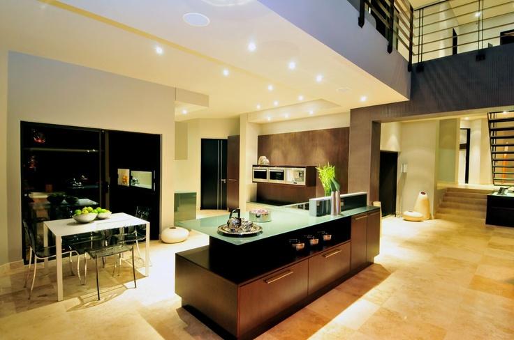Open plan, tiled floor, down lights, glass counter top island, wooden cupboards.