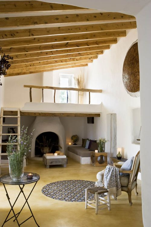 Cabin feel living room with wood beam ceiling + clay fireplace