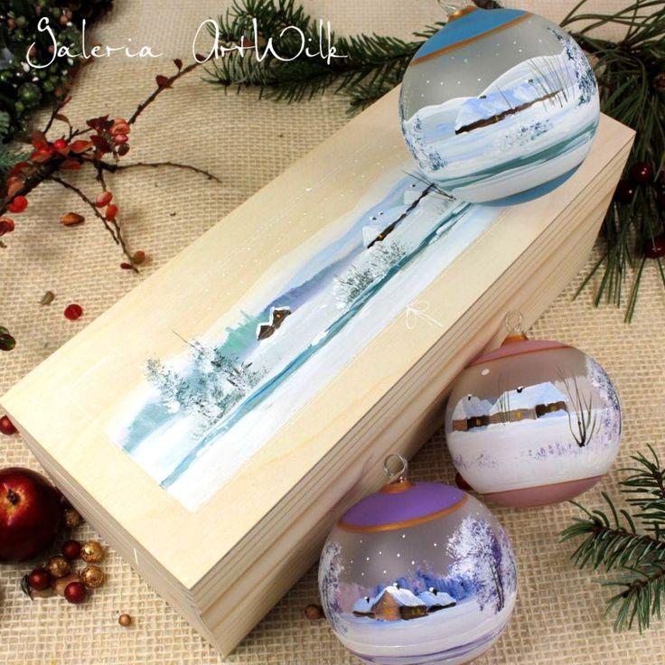Bombki wdrewnianym pudełku Trzy ręcznie malowane bombki o średnicy 80 mm wdrewnianym pudełku wypełnionym wiórami drewnianymi. Na wieczku pudełka