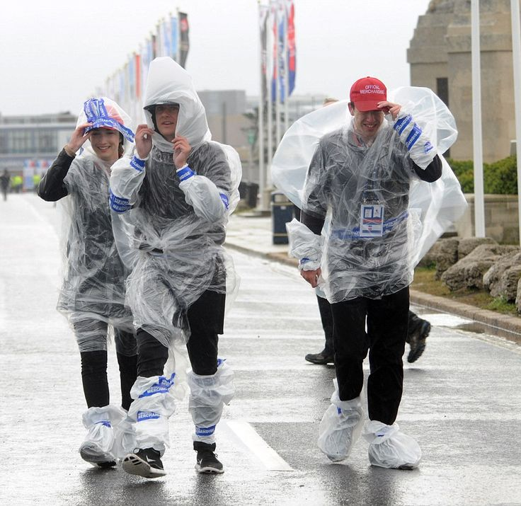 Extreme weather: Spectators warp themselves in plastic ponchos and shopping bags in a bid ...