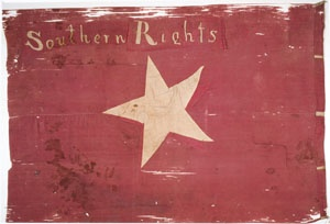 """Kansas Territory became the center of attention when it opened for settlement in 1854. When it became a state it would alter the balance of power between North and South. One group of South Carolinians formed an armed force in Kansas named the Palmetto Guards. Their red flag had a single white star and the words """"South Carolina"""" on one side and """"Southern Rights"""" on the other. They carried this flag into battle  when a proslavery force attacked Lawrence on May 21, 1856."""