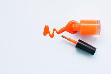 Оранжевый лак для ногтей на белом фоне с пространством для текста. Верхний вид