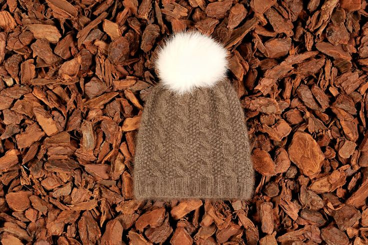Knitted beanie in brown musk ox wool with a fur tassel. Natural materials and handmade in Denmark.