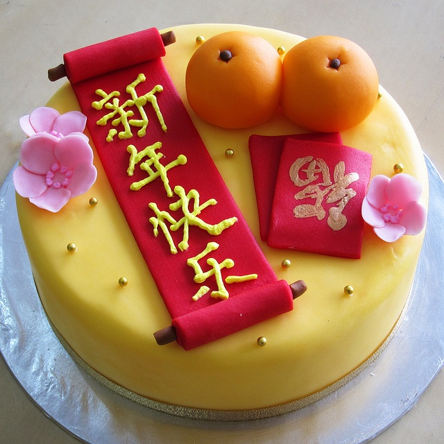 """chinese new year cake. The scroll says """"Happy New Year"""", the packets say """"fortune"""""""