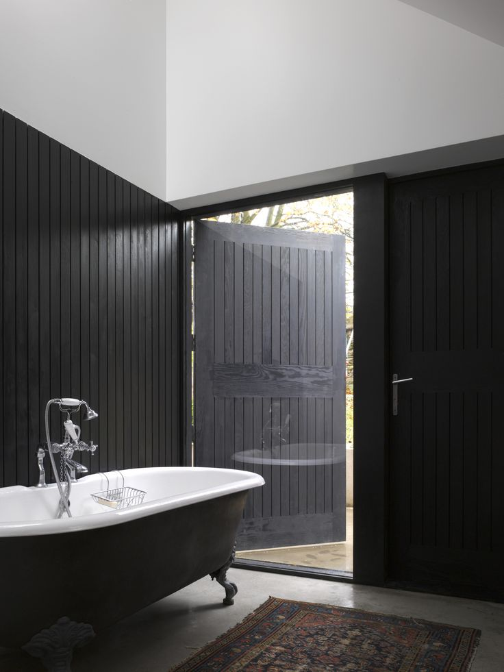 Shadow House | Jonathan Tuckey Design, Wiltshire, UK- Black stained western red cedar cladding wrapping round the bathroom and cast iron, free standing bathtub placed on a polished concrete floor.