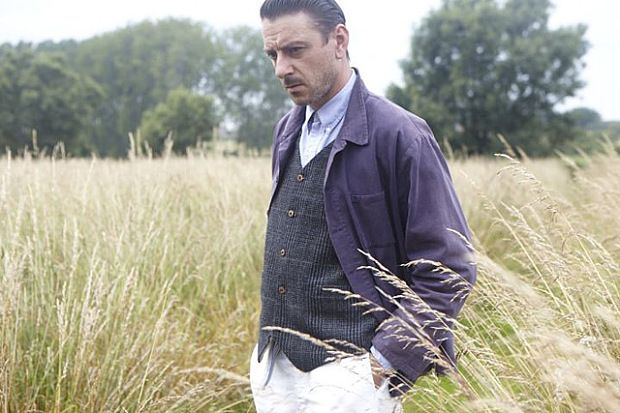 A man stands in a field wearing a waistcoat and jacket with hang in pocket.