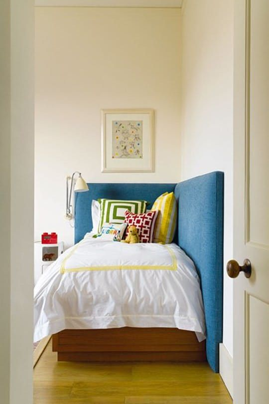Sure, beds in the corner aren't usually ideal. It's difficult to make the bed and having the biggest piece of furniture against the wall can throw off the visual balance. But sometimes, especially in a small room, it's the best or only option. Faced with this scenario, consider a wraparound, upholstered headboard. It creates soft padding against the wall for young, active sleepers and creates a comfortable, sofa-like hangout space. Here are some great examples:
