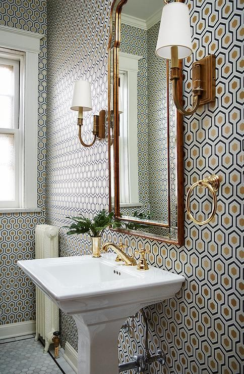 Fabulous powder room boasts walls clad in Cole & Son Hicks Hexagon Wallpaper lined with a pedestal sink accented with a gold faucet kit below an arched mirror illuminated by antique brass sconces.