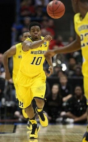 Michigan's Derrick Walton Jr. passes against Wofford during second half action of their NCAA Tournament second round game Thursday, March 20, 2014 at BMO Harris Bradley Center in Milwaukee Wisconsin.