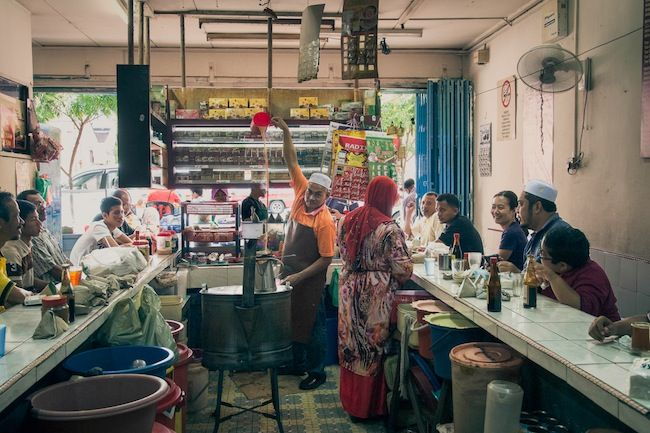 """Mohd Rudin Sulaimeen, proprietor, Kedai Kopi Din Tokyo, Kota Bharu. """"71 year old Rudin is the teh tarik maestro. He has been holding court in his coffee shop, standing behind his unusual U-shaped counter for over three decades.""""  Photographed by Kenny Loh."""