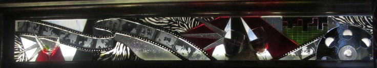 Vitrail pour un cellier dans une salle de cinéma maison.      Les coupes sont véritables, l'histoire du cinéma défile sur la bande et le verre au motif zêbré a été concu à la main.