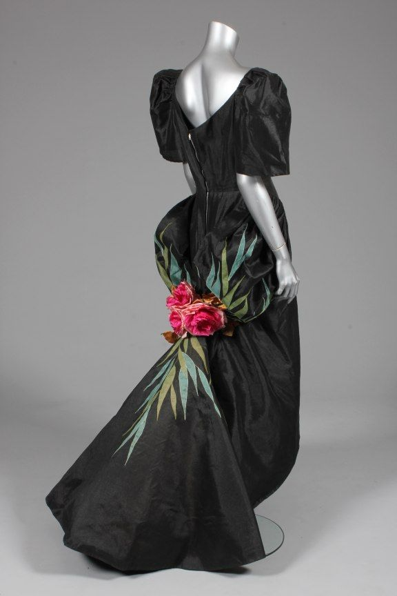 Ramon Valera black gazar evening gown, or `Terno', Philippines, late 1950s, with `butterfly' sleeves, pleated overskirt forming a puff-ball swag-effect to the back, culminating in large silk roses with appliqued foliage in shades of green,