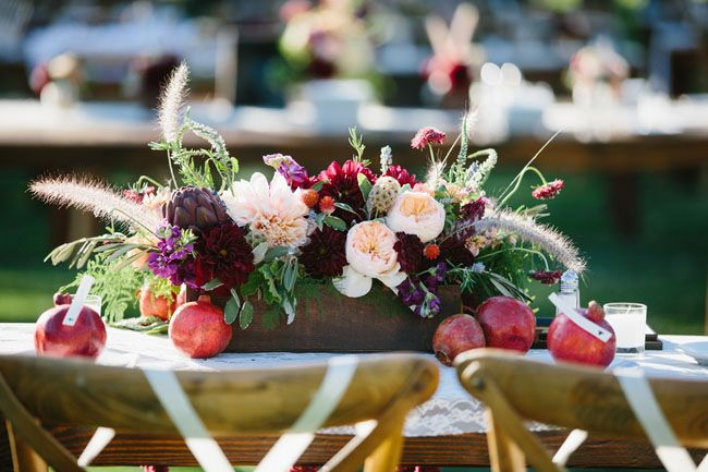 pomegranate centerpieces in this beautiful outdoor wedding has the perfect farm flair with Archive Rentals chairs