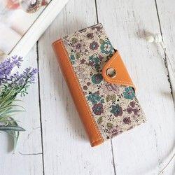 ◆FunnyGoods!◆(ファニーグッズ)※1枚布で作っているため、全ての柄が異なります。綺麗に見えるように切だして作っておりますが、あらかじめご了承くださいませ。■iPhoneSE、iPhone5、iPhone5s、iPhone5SEサイズ専用ページです。■LIBERTY リバティプリント・タナローンのSmall Susanna スモール・スザンナ生地を使い、手帳型スマホケースを作りました。上品で美しい向日葵が描かれたボタニカル調のリバティ生地です。 繊細な細い線で描かれた花と、鮮やかな空色のリバティラミネート生地が爽やかな雰囲気に仕上がっています。 淡い水色の合皮を縫い合わせました。留め具には信頼できる国内の工場から仕入れているひねり金具を使用しています。 質が良く、丈夫で使いやすいのが特徴です。留める時の「カチっ」とする音が密かに人気なんです♪■内側にはブラウンの合皮を使用。内側にはカードポケットを付けています。 駐車券やクレジットカードなどを入れておくのに便利ですよ♪ ■この形はAタイプのスマートフォンケースになります。…