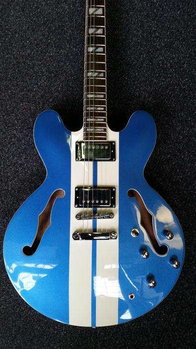 Nieuwe Indie 2Tone Stripe aangepaste blauw met witte streep ES-335-model  De Indie 2 tonen zijn zonder twijfel een van de beste semi's beschikbaar!Daarmee is cool looks en Indie bouwkwaliteit het is een geweldige live gitaar... zeer veelzijdige klinkt verstandig ofwel erg glad op de schone of echte rockin op overdrive.Deze Baby is uitgerust met Indie GR8 Alnico Humbuckers en is Super Cool met de Racing Stripe... Een uitstekende gitaar!Een moderne klinkende versie van een oude stijl gitaar in…