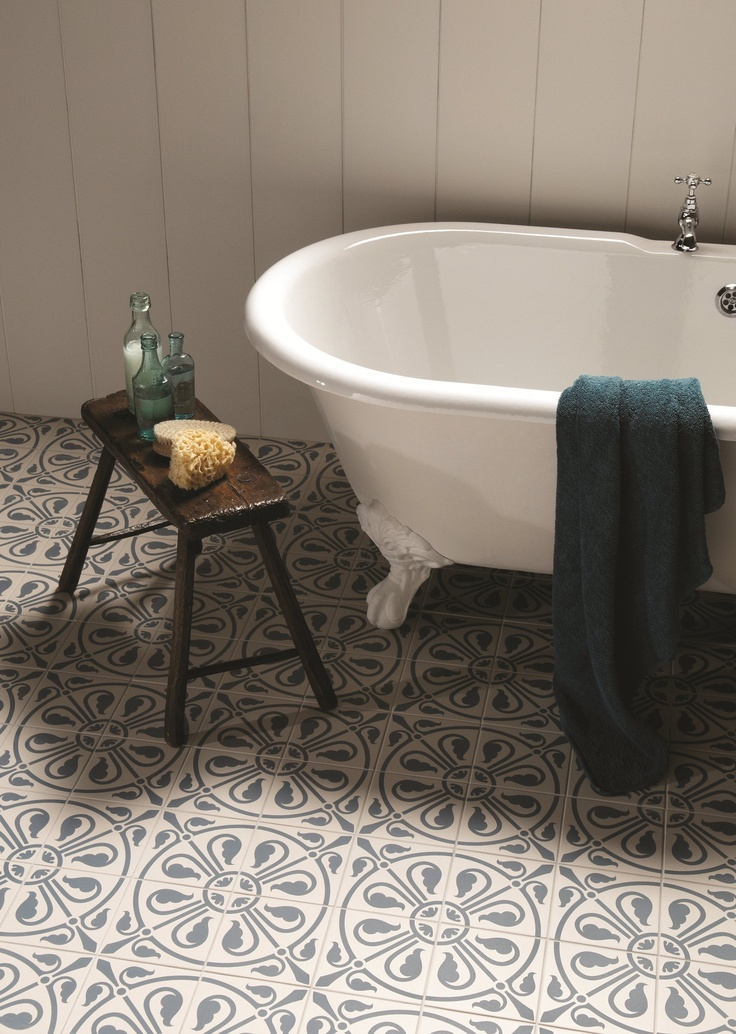 Phoenician tiles in denim from the Odyssey collection by Original Style. A patterned floor looks great with a rustic table and a clawfoot freestanding bath tub.