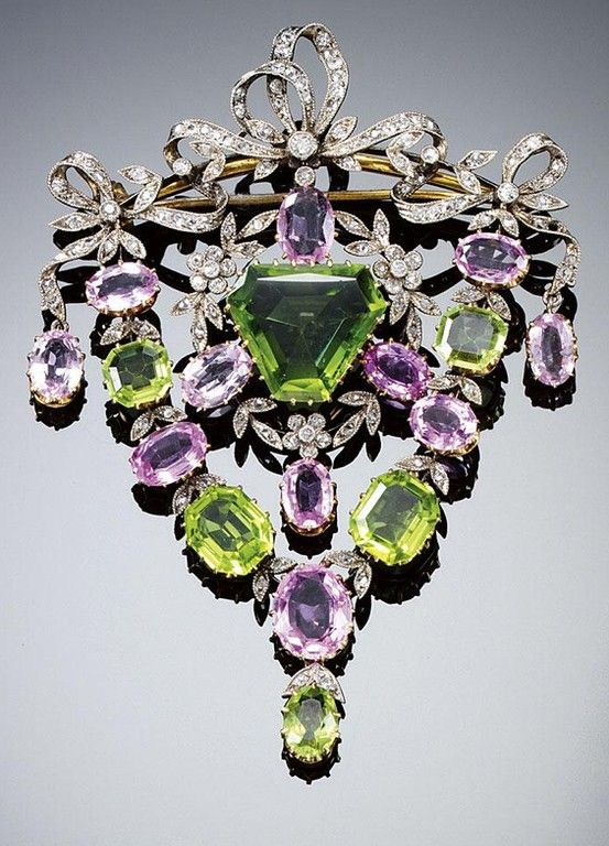 PERIDOT, PINK TOPAZ AND DIAMOND BROOCH/PENDANT, CIRCA 1900. The central swing pendant designed as a garland composed of rose- and circular-cut diamonds and oval pink topaz, centring on a modified triangular-shaped peridot, within a frame set with graduated oval topaz and octagonal peridot, to a surmount of tied ribbon bows set with rose- and circular-cut diamonds.