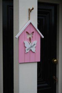 """Een roze houten vogelhuisje met de zwarte tekst """"welkom"""" op een witte vlinder -Home 26"""