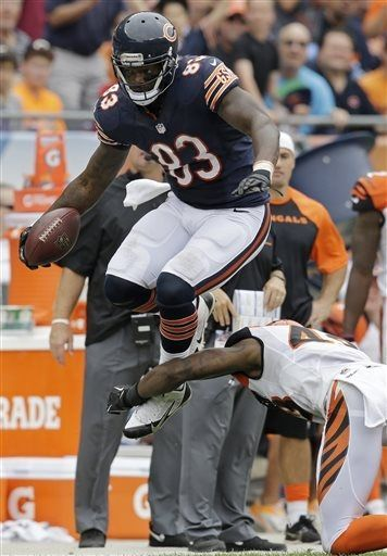 Chicago Bears tight end Martellus Bennett (83) leaps to avoid a tackle by Cincinnati Bengals safety George Iloka (43) during the second half of an NFL football game, Sunday, Sept. 8, 2013, in Chicago. (AP Photo/Nam Y. Huh)
