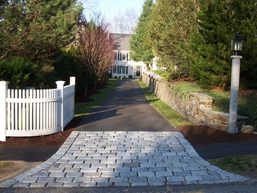 fence next to driveway. cobblestone or some type of stone at the main entrance with light post and decorative fence next to driveway r