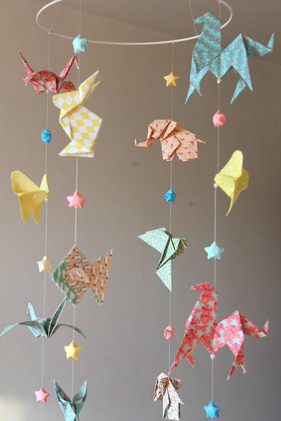 Mobile décoratif pour bébé en Origami, 16 origami animaux aux couleurs pastel et acidulées. Ce mobile animalier contient des formes dorigami animaux, dans des couleurs lumineuses, pastel. Il se compose de : - 16 origami : lapins, éléphants, grues, cheval, colombes, poissons, papillons - 12 étoiles chinoises du bonheur aux tons pastels (turquoise, rose, jaune, bleu ciel, crème)  Matériaux utilisés : papier origami à motifs, cercle métallique blanc, petites perles de fixation, fil de nylon…
