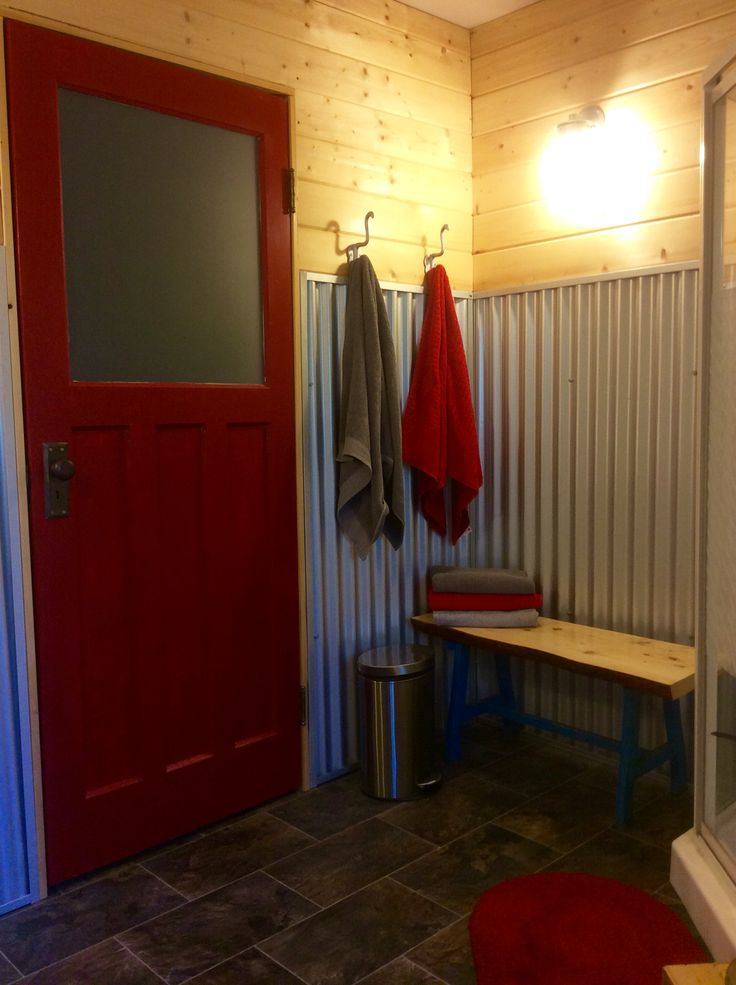 Garage conversion - We used galvanized tin and pine for the walls in the bathroom. The door was salvaged from a local business that was being torn down.
