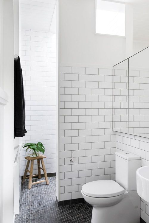 White subway tile is always the way to go in the bathroom. It's paired with contrasting floor tiling in this one for a subtle effect.