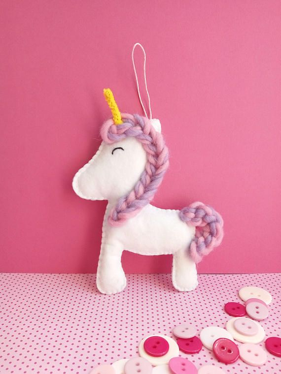 Add some magic to any girls room with this cute unicorn ornament.  --Item details-- This pretty felt ornament is made out of high quality synthetic felt fabric. Hand cut and hand sewn by me, it is filled with cotton filling and hangs from a cotton cord. The mane and tail are made out of felt yarn and the horn is made from a piece of pipe cleaner.  --Item measurements-- The unicorn ornament is measured 15 x 12 cm (aprox. 5.90 x 4.72 inches) and hangs from a cord that measures 6 cm (aprox…