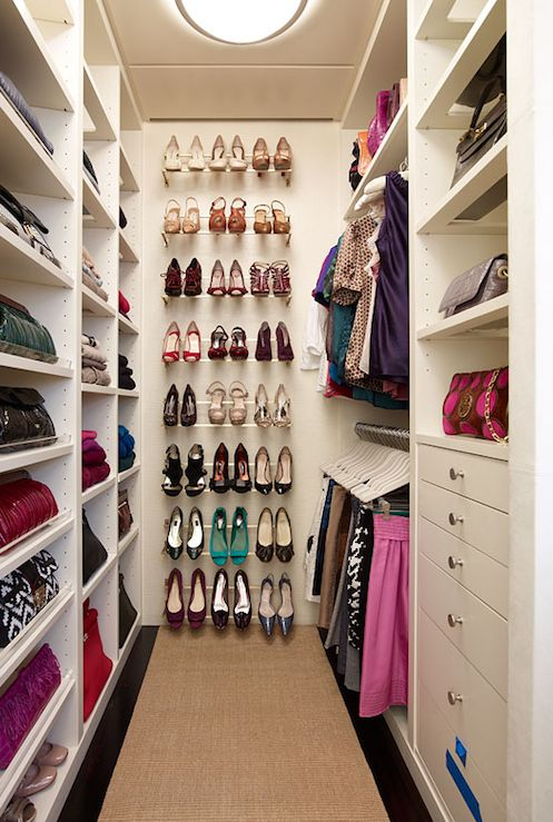 Walk-in closet with white built-ins and shoe rack.