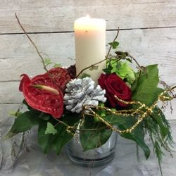 A Christmas flower arrangement in festive colours. This flower arrangement contains red roses, anthurium, pine cones and a slow burning white wax church candle with a selection of other seasonal flowers and foliages arranged in a mirrored container.
