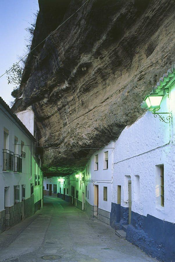 Это может выглядеть как дома в нескольких шагах от разгрома гигантской скалы, но на самом деле это город Сетенил де лас-Бодегас в Испании.  В течение своей истории местные жители строили дома в скалистых навесах ущелья.