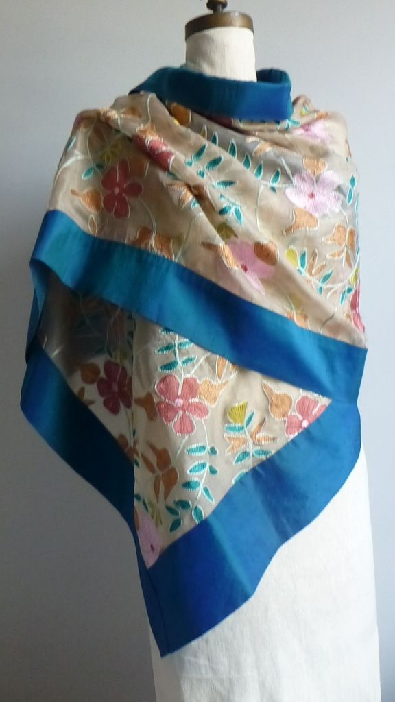 EMBROIDERED ORGANZA SHAWL -Silk- Teal Edge. Turquoise, Pink, Maize, Ochre and Off-White This absolutely exquisite and delicately luxurious shawl has been handcrafted from embroidered silk organza and silk shantung. The floral detailing has been rendered in turquoise, pink, maize and ochre thread, on a pale off-white background. This shawl has been hand-finished to the highest couture standards, including hidden seams.